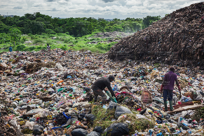 Nigeria. Enugu State. Enugu. Garbages collector on garbage heap. Scavengers at work. The open air and uncontrolled rubbish dump shows the failure in the solid-waste management. Enugu is the capital of Enugu State, located in southeastern Nigeria.  2.07.19 © 2019 Didier Ruef