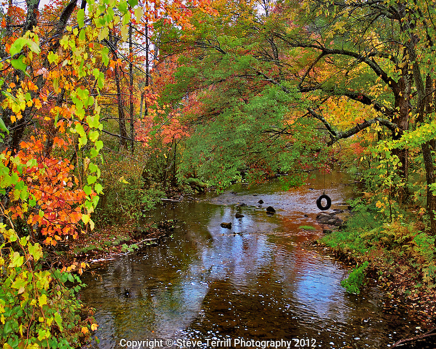 USA, New York, fall colors lining Brant Creek Warren County New York
