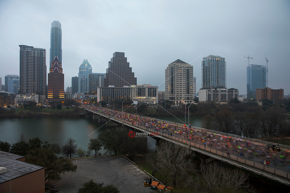 Slow shutter shows blurred motion running speed of the Austin Marathon runners on the Congress Avenue Bridge over Lady Bird Lake against the Austin Skyline after race start on a cool and moody February morning.