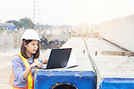2DYGP0E Beautiful Asian female engineer in white safety hard hat using laptop computer notebook doing job at construction site outside office. Idea for modern