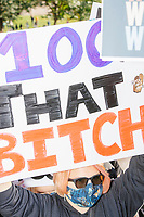 """A crowd gathers in Boston Common for the 2020 Women's March protest in opposition to the re-election of US president Donald Trump in Boston, Massachusetts, on Sat., Oct. 17, 2020.<br /> The sign here reads """"100% that bitch."""""""