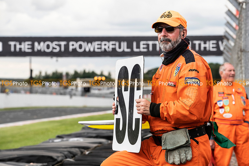 The first few laps were under a safety car as the Marshall holds the notice out during the British GT & F3 Championship on 11th July 2021