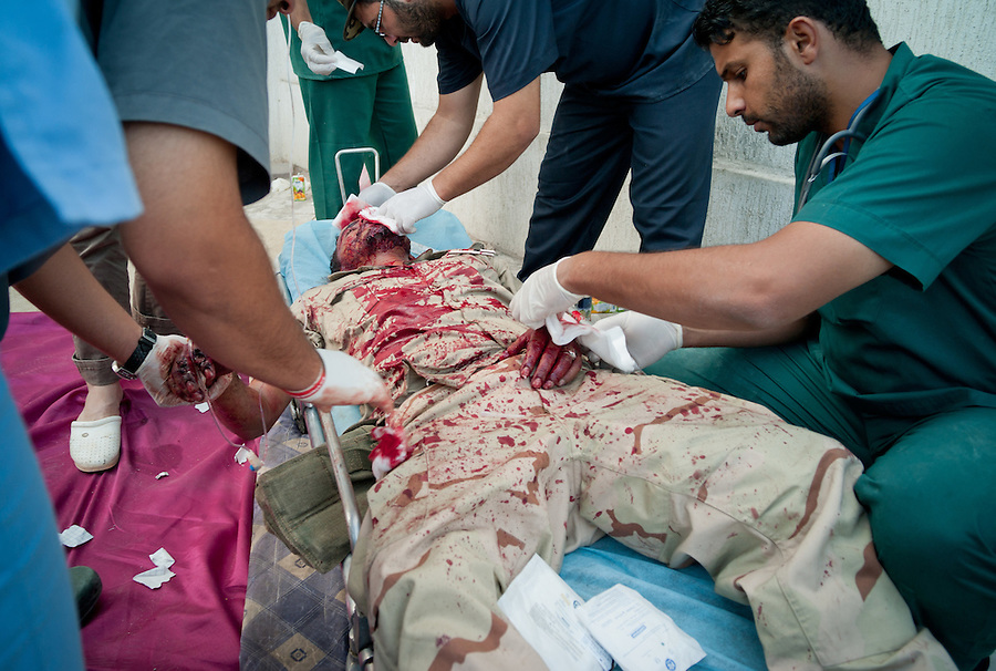 Anti-Gaddafi fighter being treated for blast wounds at a makeshift front line clinic on the side of the road in Sirte, Libya.