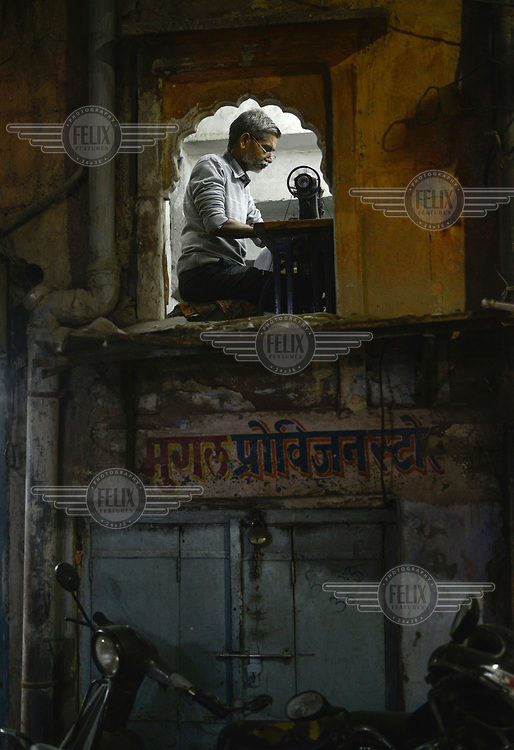 A tailor framed by an ancient window, works seated on the floor in his tiny workshop above a shop on the Lakhara Bazaar Road.