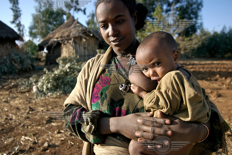 20 year old Adena Tiruneke holding her 19 month old son Mengestu in front of her hut in the village of Neguya.