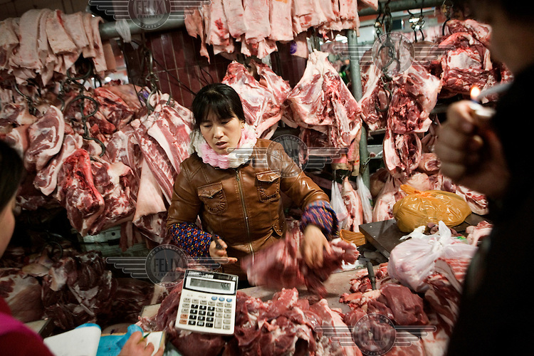 Butcher selling pork at Beijing's wet market. Pork prices have doubled in less than a year in China, reaching dangerously high levels for the average citizen. Government officials have since announced direct controls on food prices; requiring large producers of pork and other staple products to obtain government approval before raising prices.