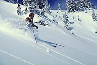 Male snow skier cuts through deep, uncut powder on an open slope. sports, skiing. Utah, Alta Ski Resort.