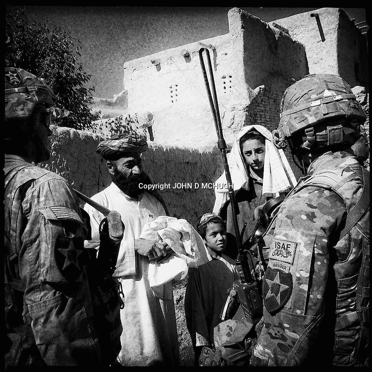 Soldiers from Bayonet Company, 1-38 Infantry chat with locals after a five hour firefight with the Taliban in Pay-E Moluk village,  Panjwayi district, Kandahar, 30 April 2013. (John D McHugh)