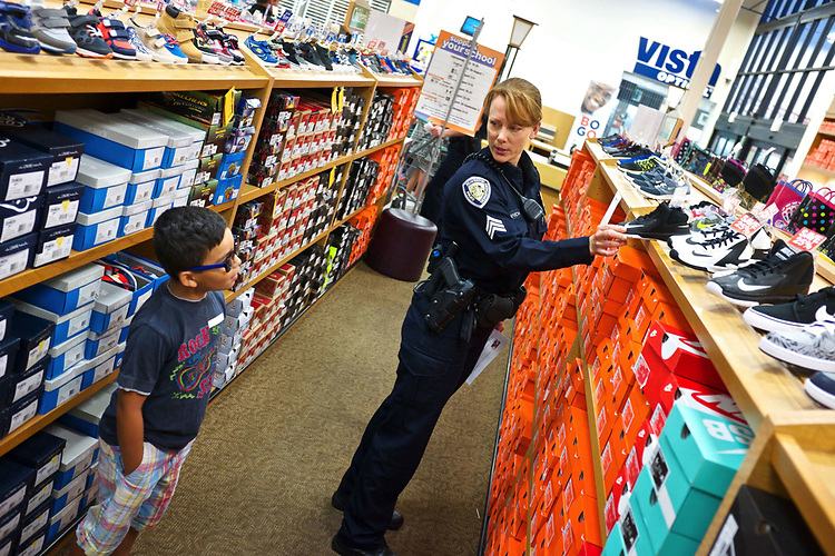 Misha Sashayvich, a police officer with the Beaverton Police Department, asks Ezekiel Lopez, 7, if he likes the shoe in her hand during the Shop with a Cop program at Fred Meyer. <br /> Photo by Jaime Valdez