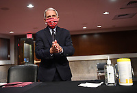 Dr. Anthony Fauci, director of the National Institute for Allergy and Infectious Diseases, cleans his hands as he prepares to testify before the Senate Health, Education, Labor and Pensions (HELP) Committee on Capitol Hill in Washington DC on Tuesday, June 30, 2020.  Fauci and other government health officials updated the Senate on how to safely get back to school and the workplace during the COVID-19 pandemic. Credit: Kevin Dietsch/CNP/AdMedia