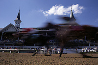 Blur of fast moving horses race down the stretch in front of the twin spires at Churchill Downs racetrack.