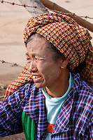 Myanmar, Burma.  Woman of Pa-O Ethnic Group at Local Market, Inle Lake, Shan State.  She has the remnants of thanaka paste on her cheeks and neck, a natural cosmetic sunscreen.