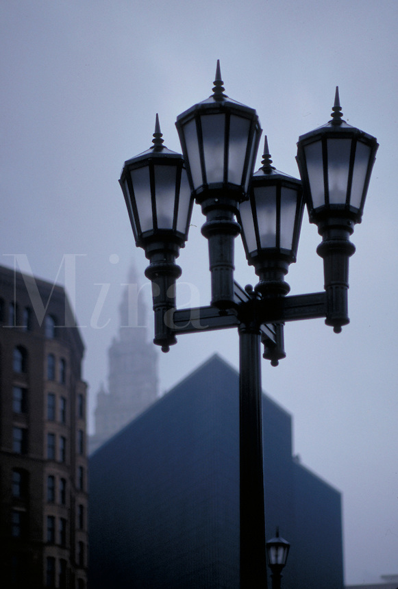 A traditional four-lamp post on a mistly morning with Cleveland's Terminal Tower in the background. Cleveland Ohio USA.