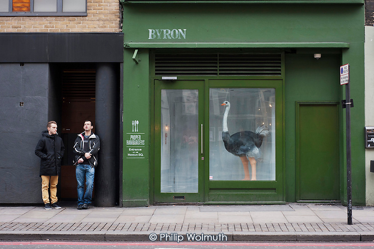Two young men stand outside a hamburger bar with an ostrich in the window.  Shoreditch, London, a run-down commercial district  also known as Silicon Roundabout, which is undergoing gentrification as it becomes a centre for web-based companies and IT start-ups.