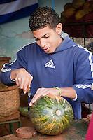 Cuba, Havana.  Young Afro-Cuban Man Cutting a Watermelon.
