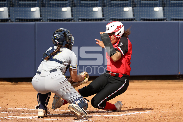 GREENSBORO, NC - MARCH 11: Delaney Cumbie #2 of UNC Greensboro tags Danielle Williams #21 of Northern Illinois University out at home plate during a game between Northern Illinois and UNC Greensboro at UNCG Softball Stadium on March 11, 2020 in Greensboro, North Carolina.