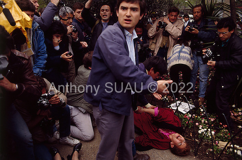 """Santiago, Chile.September 27, 1988..An anti-General Augusto Pinochet rally takes place near a prison prior to the plebiscite vote. Police confront the demonstrators at close range with tear gas...In 1988, General Augusto Pinochet ordered a plebiscite vote asking Chilean citizens whether he should continue in office. It produced a decisive """"no"""" vote and the following year he lost the first presidential election in 19 years. However, under a constitution crafted by his advisors, he remained as army commander until 1998. Pinochet continued to wield enormous power until his arrest in London on human rights charges in October 1998."""