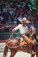 A Mexican cowboy (gaucho) on horseback swings his lasso at the Charros Rodeo Fiesta Event. San Antonio, Texas.