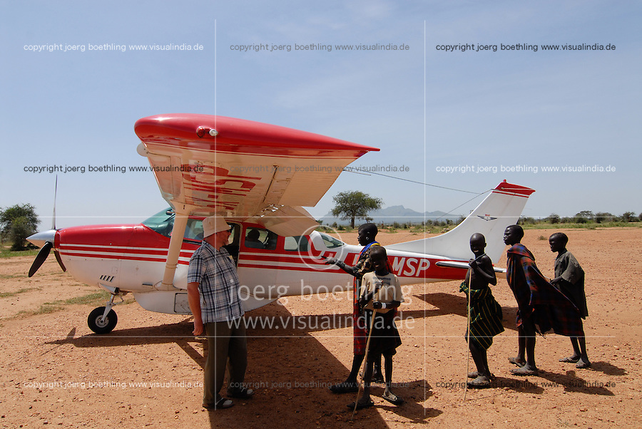 Uganda Karamoja , airstrip Kotido , Karimojong und Cessna der MAF Mission Aviation Fellowship ist ein christlicher Flugdienst, der fuer christliche Missionswerke , NGOs , Organisationen  fliegt / Uganda  Karamoja , airstrip Kotido , Karimojong and Cessna aircraft of MAF Mission Aviation Fellowship which works for christian missions, NGO, organisation to transport people and relief goods