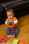 5 month old baby boy sitting without support holding toy plastic chain