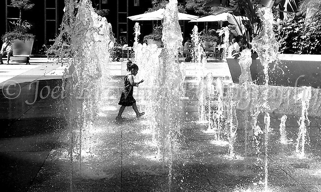 A young girl enjoys playing in the fountains at Pittsburgh's PPG Plaza on a hot afternoon.