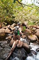 Young woman crossing a creek by balancing on a log while hiking the trail to Hanakapiai Falls, Napali Coast, Kauai, Hawaii