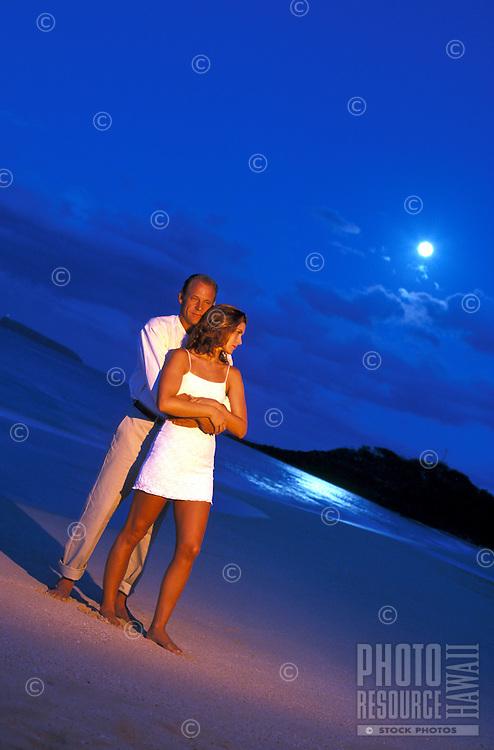 Couple embrace at Makena Beach, Maui while a full moon sets.