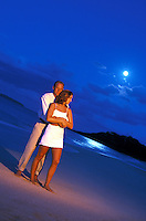Couple embrace at Makena Beach, Maui while a full moon sets.