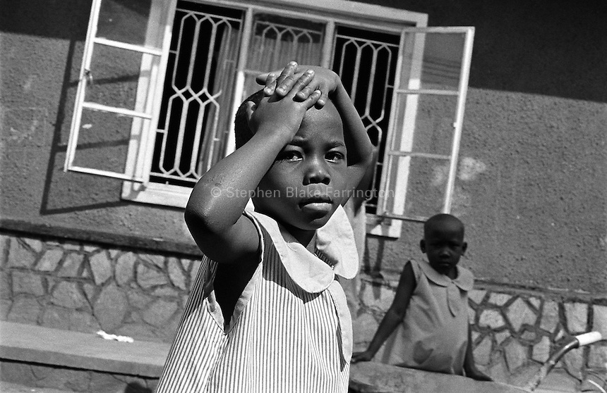 Standing in the yard at Rehaboth Integrated School. Most of the 130 plus children that attend this school are orphans due to HIV/AIDS. Uganda has an estimated 1.5 million people infected with HIV/AIDS and contains over 1 million orphans. Bugembe, Jinja District, Uganda, Africa. June 2004 © Stephen Blake Farrington