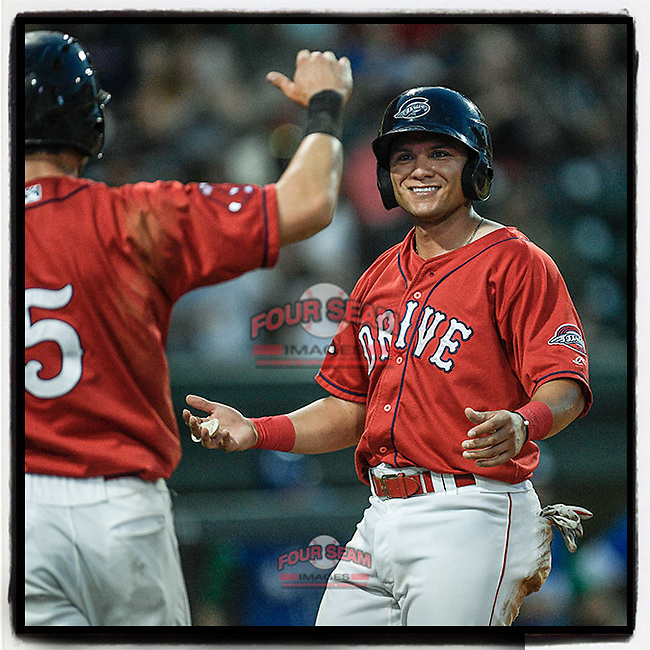 Shortstop Frankie Rios (12) of the Greenville Drive is congratulated by Jordan Wren (5) after both scored in the second inning of a game against the Lexington Legends on Saturday, September 1, 2018, at Fluor Field at the West End in Greenville, South Carolina. Greenville won, 9-6. (Tom Priddy/Four Seam Images)