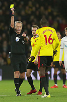 (L-R) Referee Martin Atkinson shows a yellow card to Abdoulaye Doucoure of Watford for his foul against Jordan Ayew of Swansea City during the Premier League match between Watford and Swansea City at the Vicarage Road, Watford, England, UK. Saturday 30 December 2017