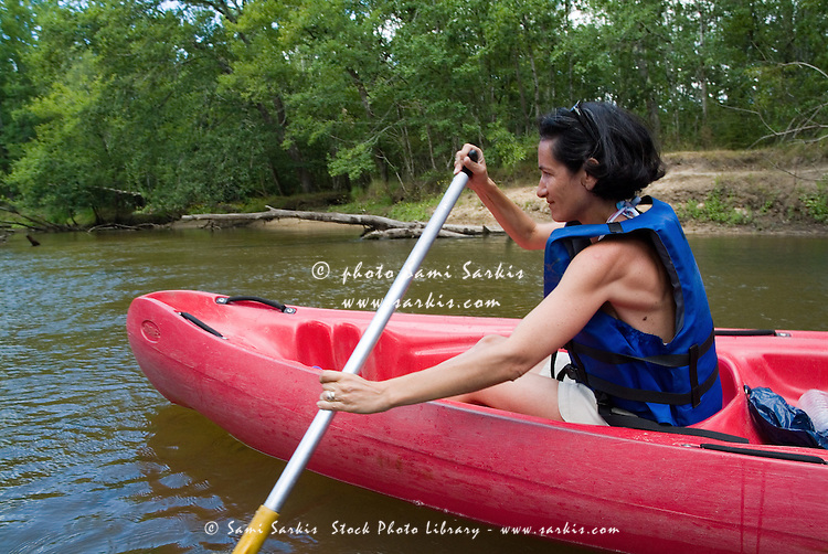 Woman canoeing on the Eyre river, Aquitaine, France.