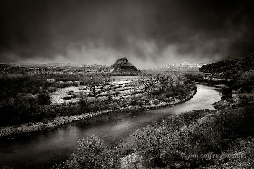 The Chama River flows just north of Abiquiu, New Mexico under a stormy spring sky.