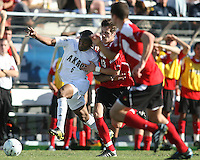 Darlington Naqbe #6 of the University of Akron struggles to get free from Josh Lipka #13 of the University of Louisville during the 2010 College Cup final at Harder Stadium, on December 12 2010, in Santa Barbara, California.Akron champions, 1-0.