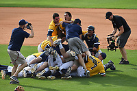 The UNC Greensboro Spartans pile on each other after beating the Furman Paladins in the title game of the Southern Conference Championship series on Sunday, May 28, 2017, at Fluor Field at the West End in Greenville, South Carolina. UNCG won, 13-1. (Tom Priddy/Four Seam Images)