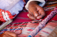 An indigenous woman weaves a table runner in Cusco, Peru, on May 19, 2008. The iconography expressed on the textiles is traditionally used in the communities and it represents the life and environment of their inhabitants, maintaining their cultural traditions and the identity of their people.