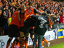 Dundee Utd's Mario Bilate punches a Dundee fan as he comes onto the park as they celebrates the late winner.