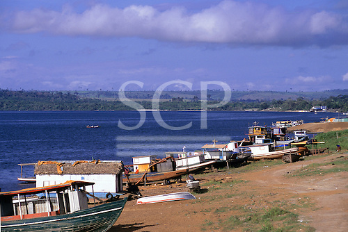 Altamira, Brazil. View of the Xingu riverside with river boats and deforested cattle ranching land beyond.