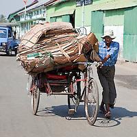 Myanmar, Burma, Yangon.  Recycling.   Rickshaw Driver Walks a Load of Cardboard to a Recycling Station.