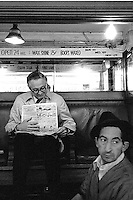 Man looks at newspaper at shoeshine stand. Bootblack. White collar and blue collar worker. Social class. Economic disparity. Houston Texas.