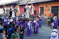 Antigua, Guatemala.  Cucuruchos Carrying Religious Figures in a Procession during Holy Week, La Semana Santa.