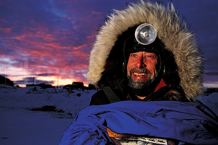A smiling, male Iditarod musher in fur-lined coat and headlamp at sunset. Alaska.