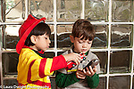 Education preschool 3-4 year olds two boys playing together in dressup costumes in pretend play area one boy talking to the other about how he is using a telephone gesturing with toy fire truck