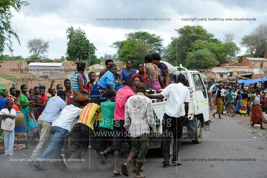 Zambia, Sinazongwe, rural market in village, men push a breakdown mini truck overloaded with women group / SAMBIA, Sinazongwe Distrikt, laendlicher Markt an einer Strasse im Dorf