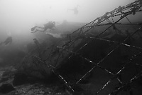 Divers explore a liveaboard wreck at Beacon Reef, Similan Islands, Andaman Sea, Thailand, Indian Ocean
