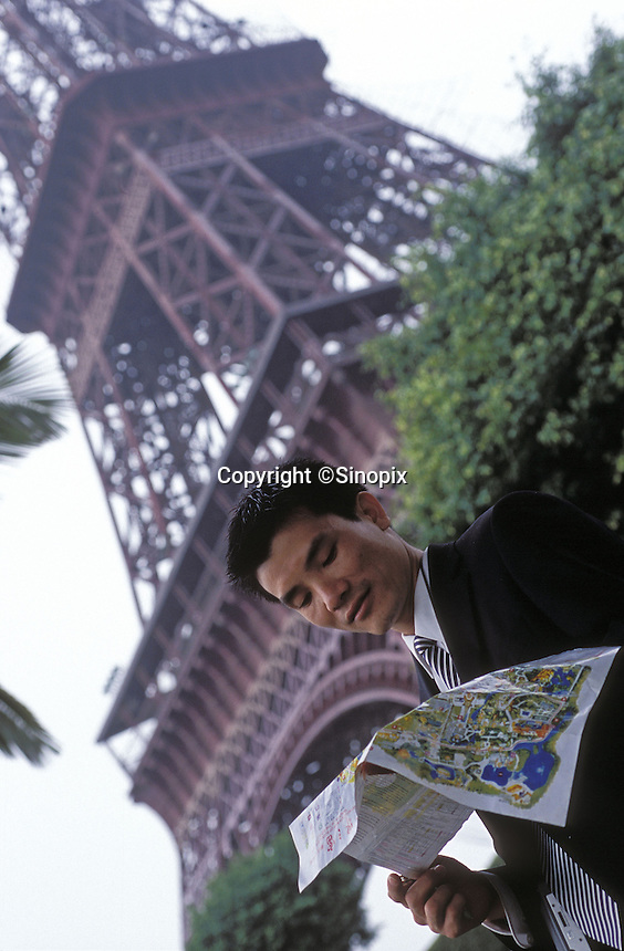 Chinese tourists under the Eiffel Tower at Windows of the World amusement park in Shenzhen, China. The amusement park has copied many of the worlds most famous monuments and attractions, mostly in minature and attracts millions of tourists annually.