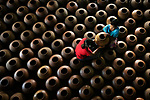 """Workers make finishing touches to hundreds of clay pots before they head off to be kiln dried.<br /> <br /> Zay Yar Lin captured these images in the town of Twantay, near Yangon, Myanmar which is known for its thriving pottery industry.  After the pots have been formed from clay they are left to dry in the sun, before this process of smoothing the surface with the stone and the final step of them being kiln dried.<br /> <br /> Zay said """"The pair are rubbing earthen pots with polished stone before drying them in the kiln.  The clay from local river beds makes Twantay a special pottery town of Myanmar.""""<br /> <br /> """"For centuries, the people of Twantay have lived off their pottery skills. Even today, their pots are of huge demand throughout Myanmar.   They can make 200 pots or more per day.""""<br /> <br /> Please byline: Zay Yar Lin/Solent News<br /> <br /> © Zay Yar Lin/Solent News & Photo Agency<br /> UK +44 (0) 2380 458800"""