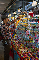 French Quarter, New Orleans, Louisiana. Tourist Examining Toy Dolls in the French Market.