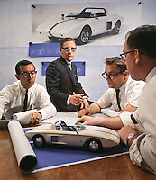 Ford Executive Engineer Roy Lunn (center) and assistants Chuck Mountain (L), Ed Hull (middle R) and Jim Mason (R) study Ford Mustang 1 model, which they designed in 1962; their concept car inspired the Mustang that went into mass production in 1964. Ford Motor Company, Dearborn Michigan, 1966. Photo by John G. Zimmerman.