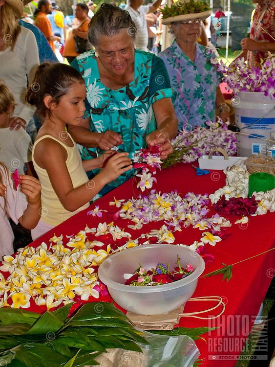 Child and Hawaiian aunty lei making at King Kamehameha Day Parade festival, King Kamehameha Park, North Kohala, town of Kapa'au.